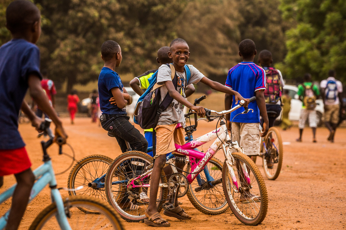 Kamsar, prefecture of Boké, Guinea. Children drive their bike across the youth centre.